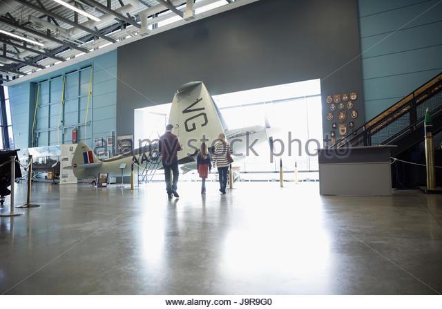 Family walking toward propellor airplane in war museum hangar - Stock-Bilder