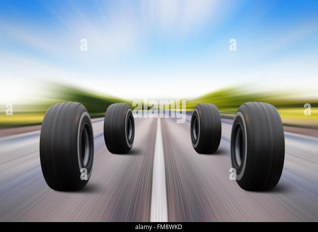 four automobile wheels rush on the road with high speed - Stock Image