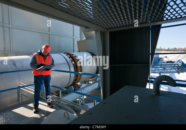 Engineer recording data at material plant - Stock Image