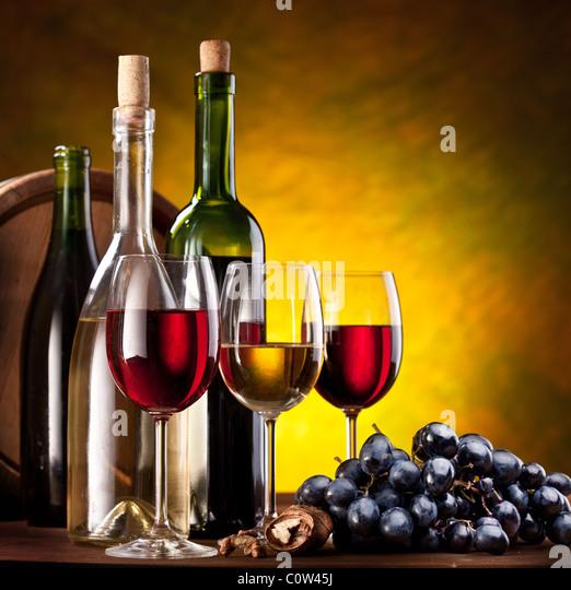 Still life with wine bottles, glasses and oak barrels. - Stock Image