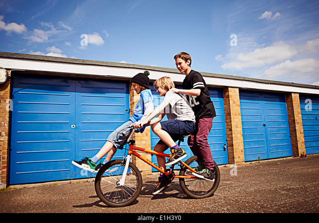 Boy giving two friends a ride on bike - Stock-Bilder