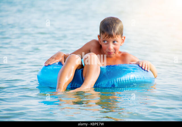 boy with cunning eyes sitting in inflatable ring and having fun in sea - Stock Image