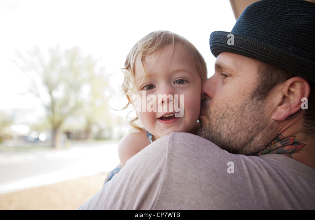 Dad with tattoo on neck kisses two year old daughter. - Stock-Bilder