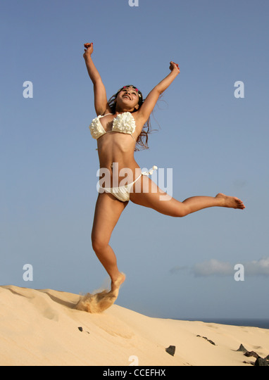 Indonesian Girl in a Cream Bikini Jumping for Joy on the Sand Dunes of Corellejo Nature Reserve, Fuerteventura, - Stock Image