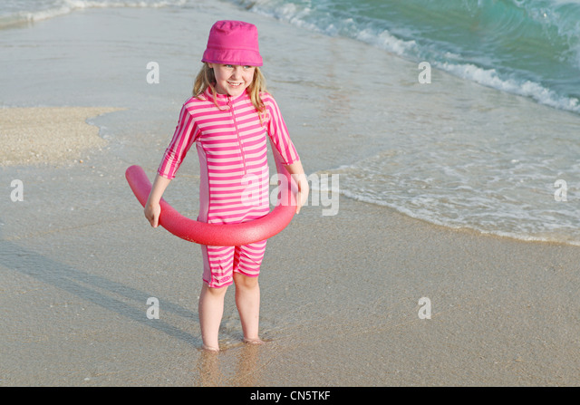 young child on beach vacation with sun protection suit and hat. - Stock Image