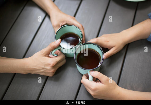 Two people seated at a table, drinking coffee, viewed from above. - Stock Image