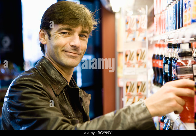 Man at soft drink cooler in convenience store - Stock Image