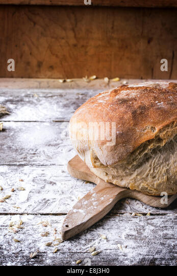 Fresh homemade bread on wooden cutting board with vintage knife served over wooden table with flour. See series - Stock Image