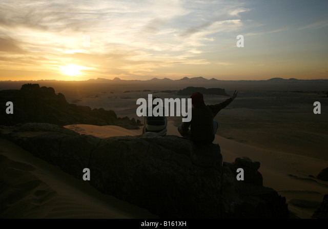 Couple looking at sunset Tagelment Samedat Tassili Ahaggar Sahara desert Algeria - Stock Image