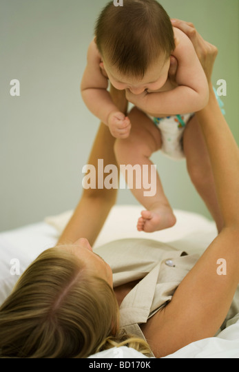 Mother lying on back holding up baby - Stock Image