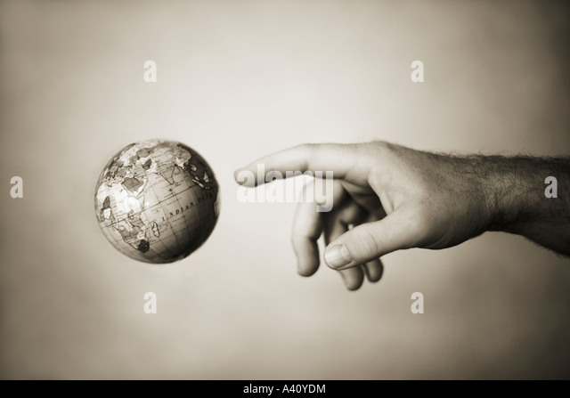 Hand reaches out for globe - Stock Image