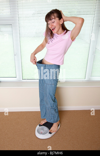 young woman happy to have lost weight - Stock Image