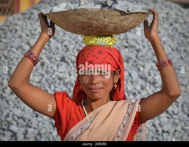 Closeup street portrait of a sari-clad mature Indian Adivasi tribal woman, carrying on her head a metal bowl with - Stock Image