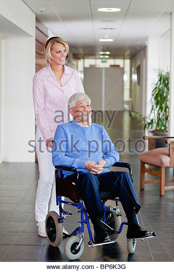 A care assistant pushing a senior man in a wheelchair - Stock Image