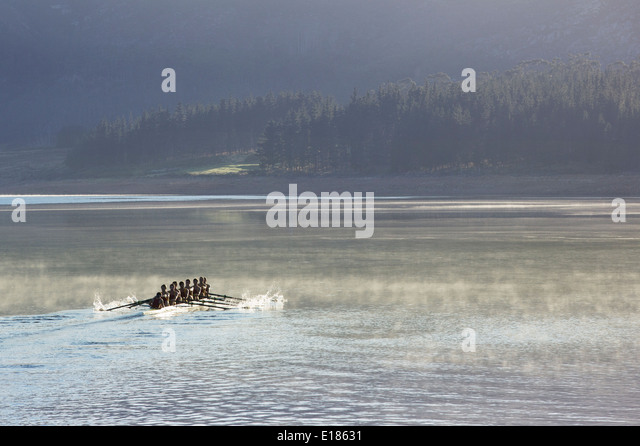 Rowing crew rowing scull on lake - Stock Image