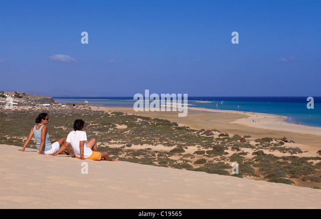 A couple sitting on a sand dune overlooking the Playas de Sotavento beach, Fuerteventura, Canary Islands, Spain, - Stock Image