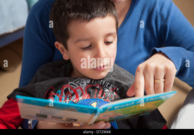 Mother helps child to read - Stock Image