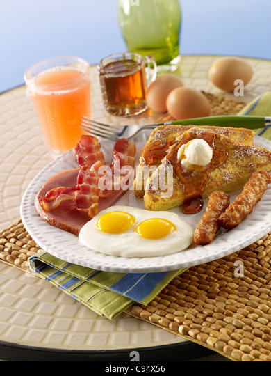 French toast served with eggs, bacon, sausage and ham - Stock Image