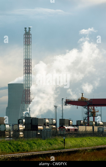 Containers on train by chemical plant - Stock Image