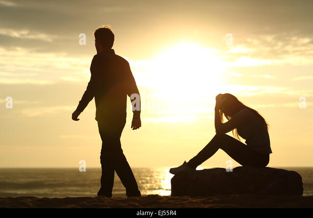 Couple silhouette breaking up a relation on the beach at sunset - Stock Image