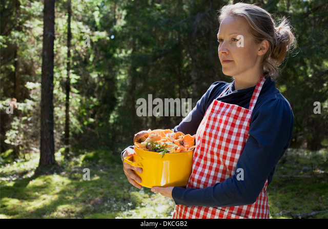 Woman in forest with mushrooms in saucepan - Stock Image