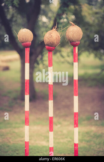 three coconuts on red and white poles forming a coconut shy at a fair.  This image has been treated with a retro - Stock Image