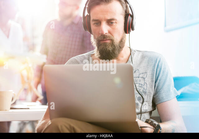 Serious male design professional with headphones using laptop in office - Stock-Bilder