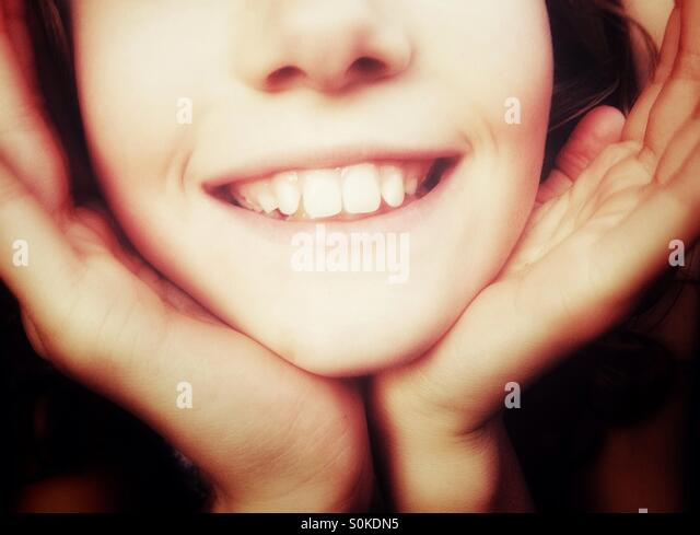 Close up of smiling girl with face cupped in her hands - Stock Image