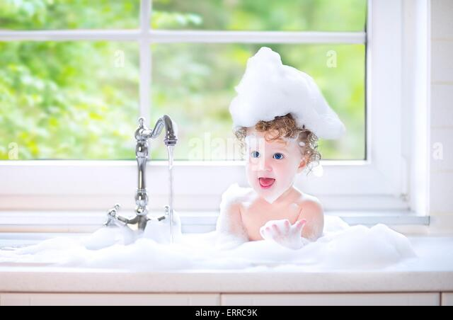 Funny little baby girl with wet curly hair taking bath in a kitchen sink with lots of foam playing with water drops - Stock Image