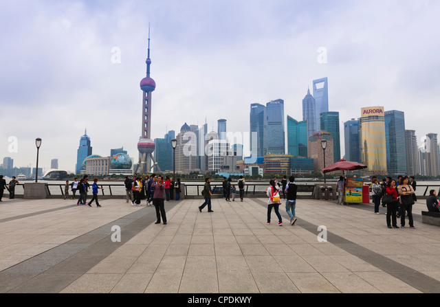 Pedestrians and tourists on the Bund, the futuristic skyline of Pudong across the Huangpu River beyond, Shanghai, - Stock Image