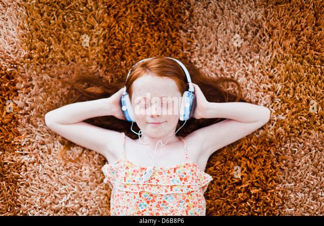 Girl listening to headphones on carpet - Stock-Bilder