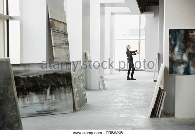 Art dealer examining painting in art gallery - Stock-Bilder