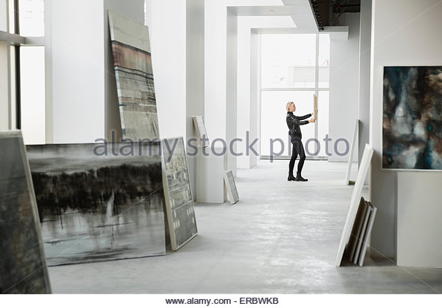 Art dealer examining painting in art gallery - Stock Image