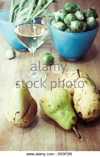 Fruits and vegetables with a glass of wine on butcher block counter top - Stock Image