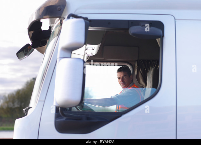 Truck driver in cab - Stock Image