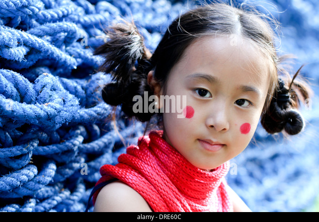 Asian girl in front of blue rope wall - Stock Image