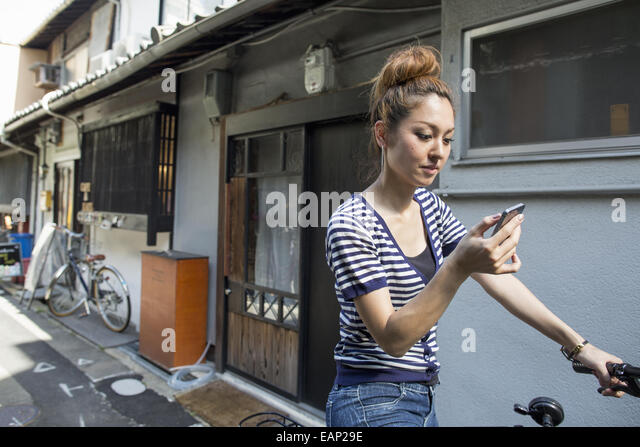 Woman standing outdoors, looking at cellphone. - Stock Image