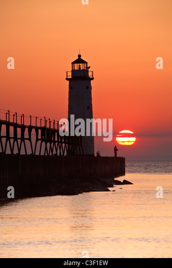 A lone fisherman is silhouetted at the base of the lighthouse on a summer evening at 5th Avenue Beach in Manistee, - Stock Image