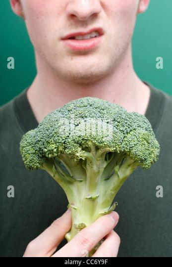 A man disliking broccoli - Stock Image