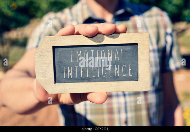 closeup of a young caucasian man showing a label-shaped chalkboard with the text emotional intelligence written - Stock Image