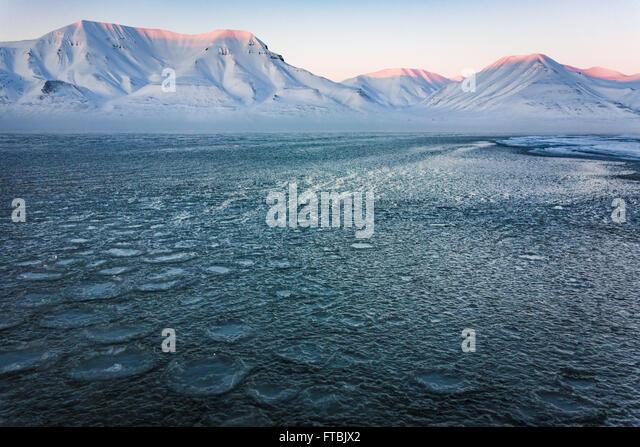 Sunset frozen shoreline at Sjøskrenten beach with views to Hiorthfjellet, Longyearbyen, Spitsbergen, Svalbard. - Stock Image