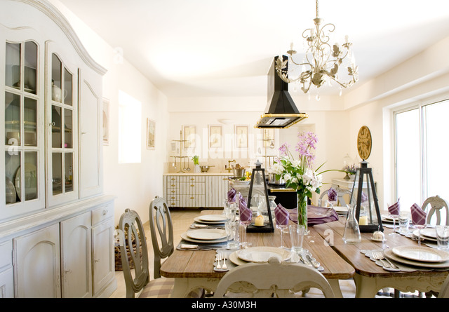 Kitchen with Chandelier above double table with place settings ready to eat - Stock Image