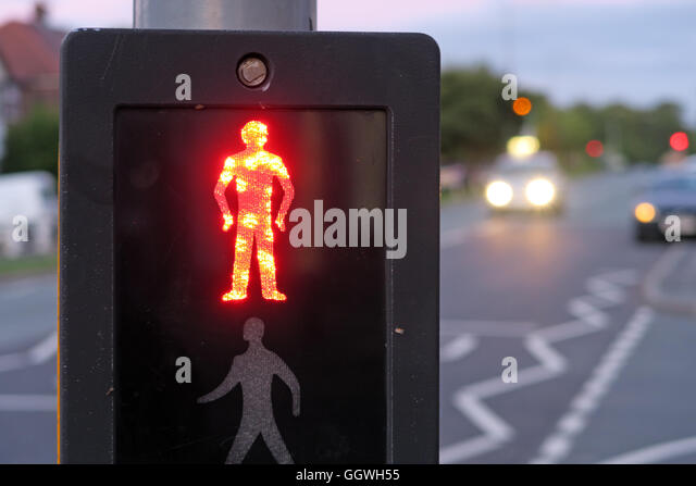 Red man at UK Pelican Crossing, with evening traffic in background - Stock Image
