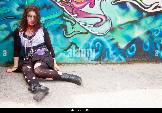 Young female teenage street theatre actress acts in horror story with fake blood Albert Dock Liverpool Lancashire - Stock-Bilder