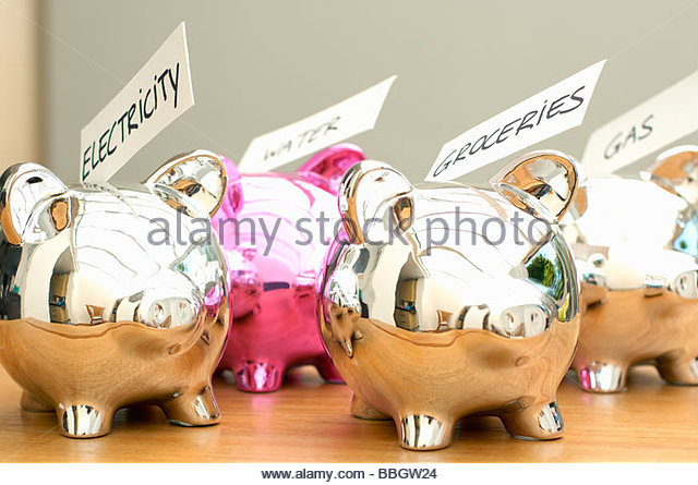 Four piggybanks with labels, focus on piggybanks with electricity and groceries label, close-up, Den Haag, Netherlands - Stock Image