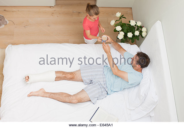 Daughter bringing coffee to father with broken leg - Stock Image