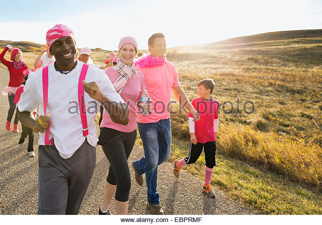Group in pink walking in charity race - Stock Image