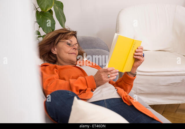 Senior woman reading a book while lying on sofa at home, Munich, Bavaria, Germany - Stock-Bilder