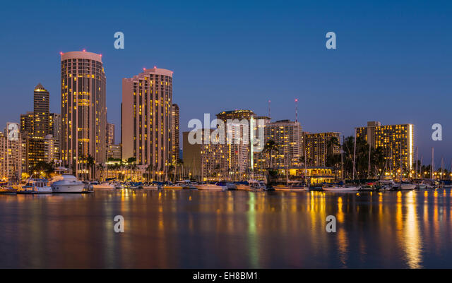 Skyline of Waikiki district, Honolulu, Hawaii at night / dusk with boats in Ala Moana harbor and Hilton Hawaiian - Stock Image