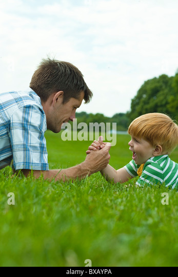 Boy and father arm wrestling - Stock Image